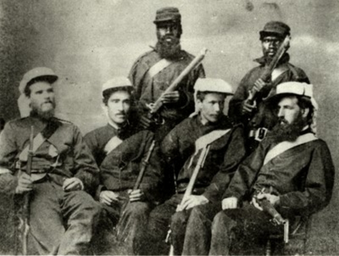 Clermont Gold Escort, 1867.  (Sitting, L-R) Constables John Power, Patrick Cahill, George Gildea, Sergeant James Julian.  (Standing) Unidentified troopers, Native Mounted Police.  Courtesy of the Queensland Police Museum (Cat. No. PM0680a).