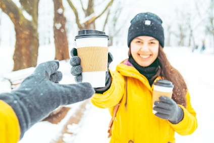 woman handing coffee to friend in snow edited.jpg