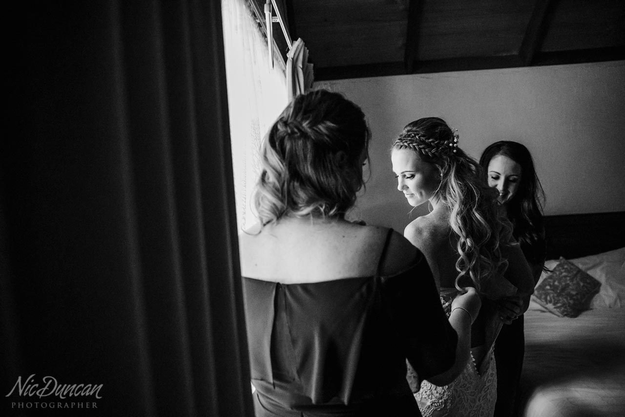 Bridesmaids helping the bride with her dress