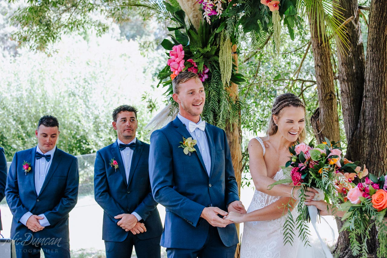 Bride handing her flowers to her bridesmaid