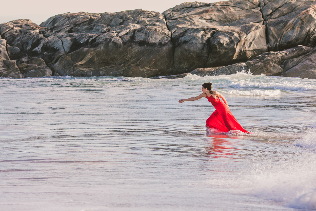 Portrait of a lady in red dress in the ocean,
