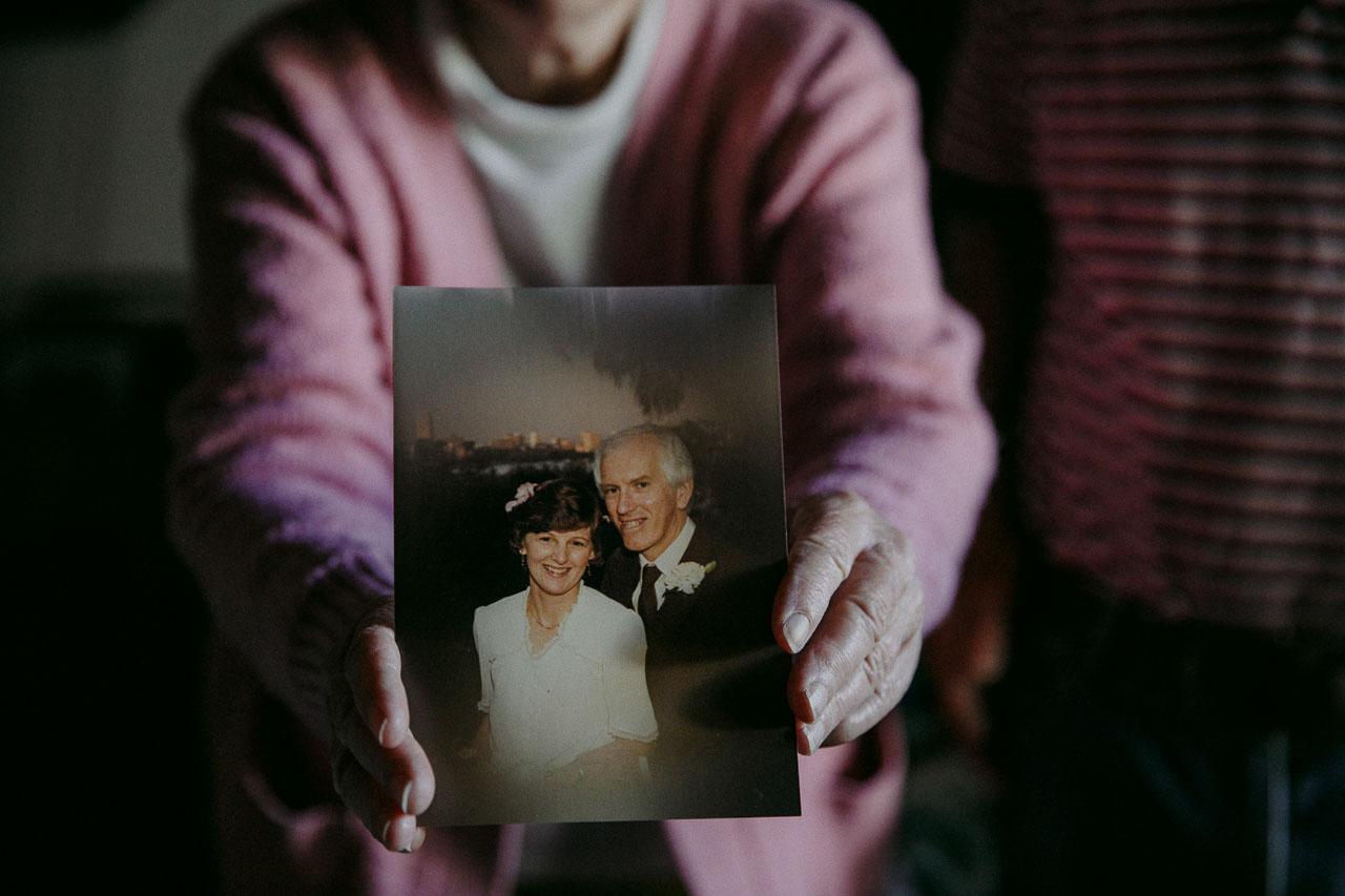 Old lady holding her wedding photo