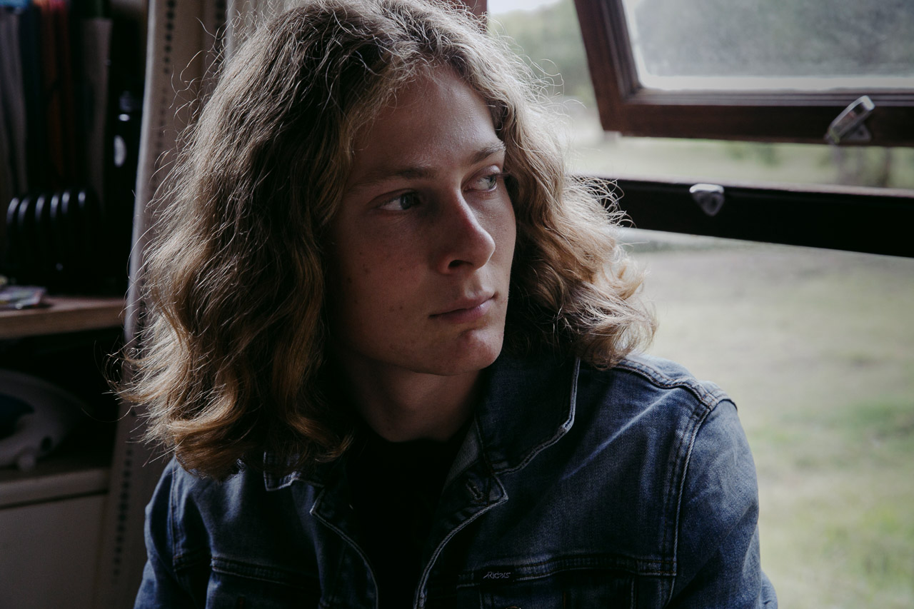 Portrait of a teenager looking out of his window