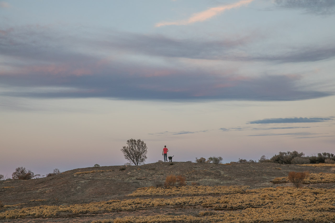 Man and dog walking on top of a granite outcrop in WA's wheatbelt at sunset