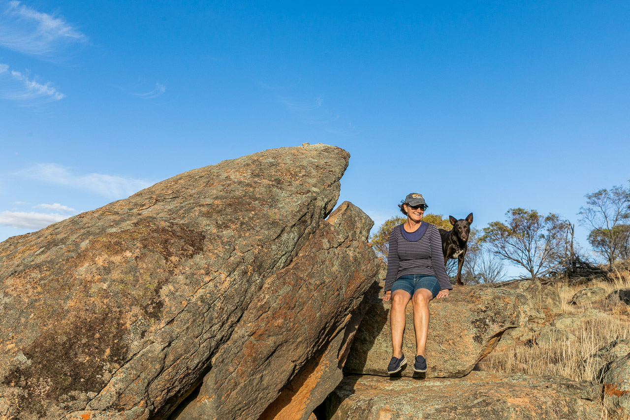 Farmer and her red cloud kelpie sheepdog, sitting on a granite outcrop in the wheatbelt, WA