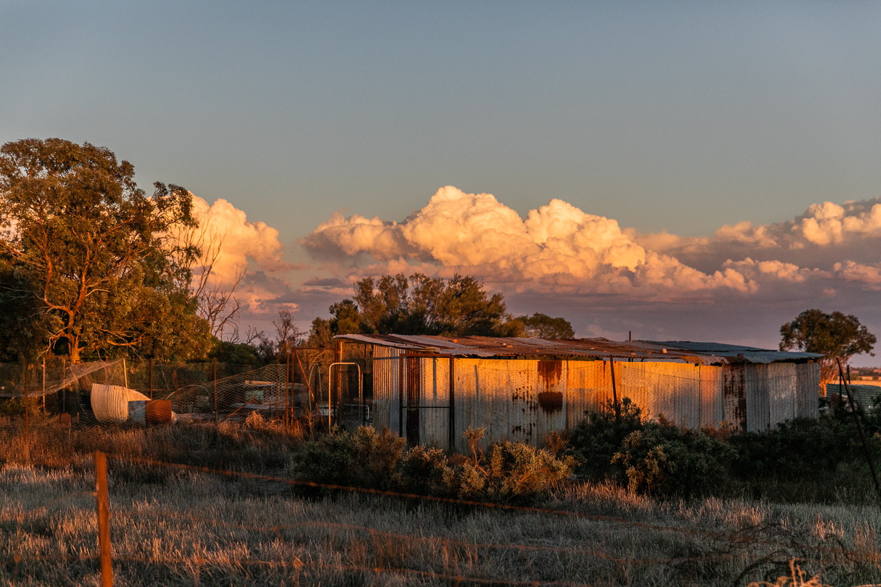 Old rusty farm sheds at sunset with storm clouds forming