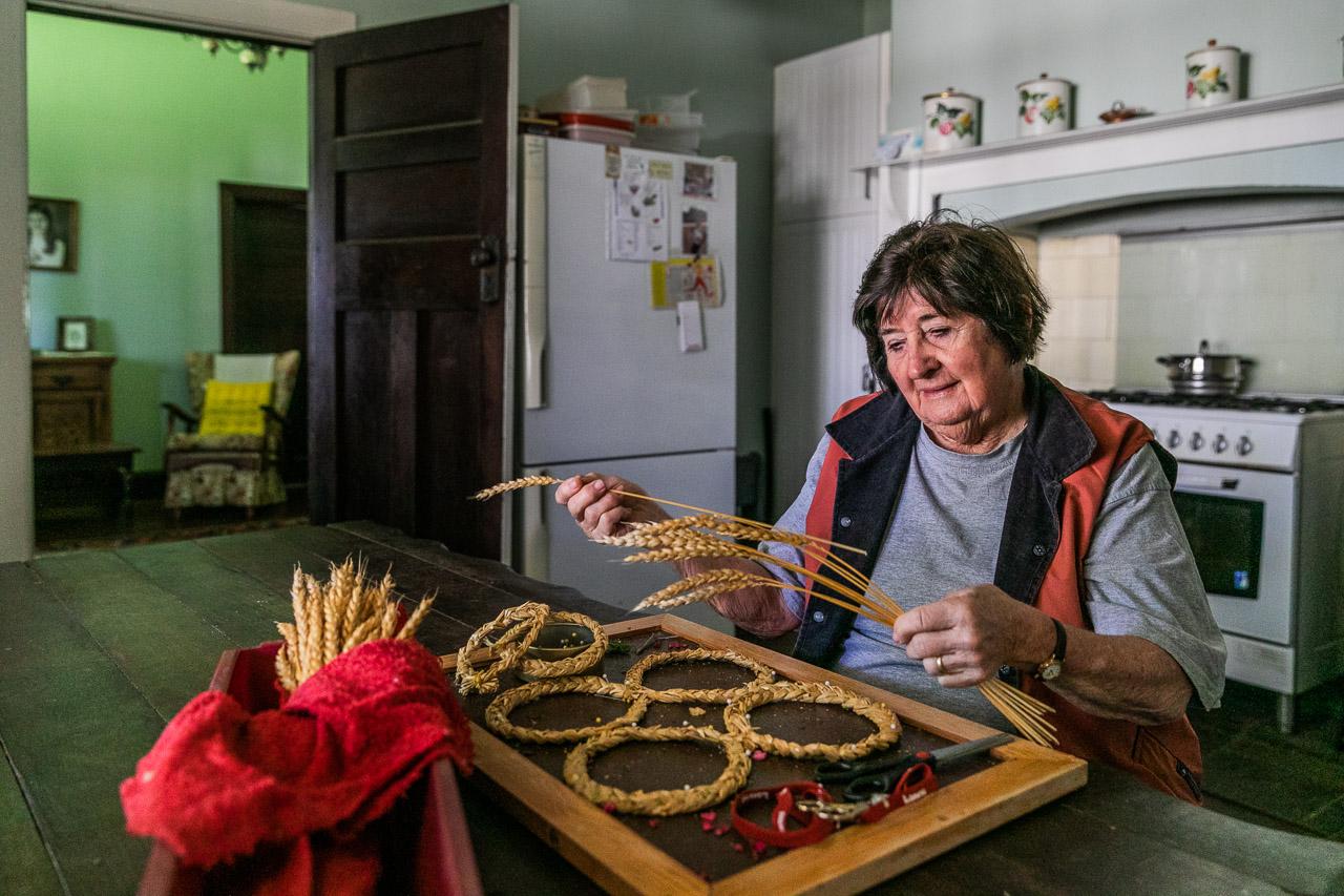 Lesley McNee creates an art piece using wheat to celebrate the Koorda CWA's birthday