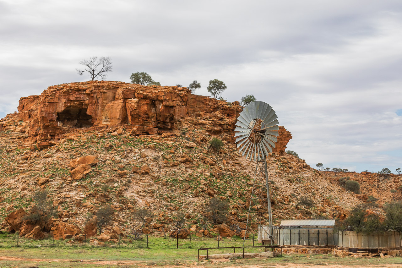 A windmill and water tank in front of a breakaway on a station in Western Australia