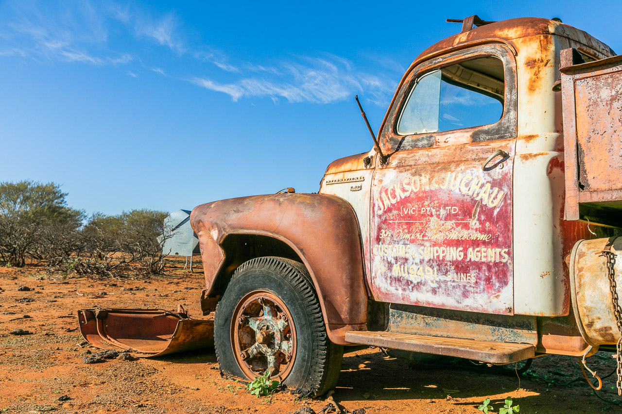 Old rusty vehicles and faded signage at Carey Downs Station