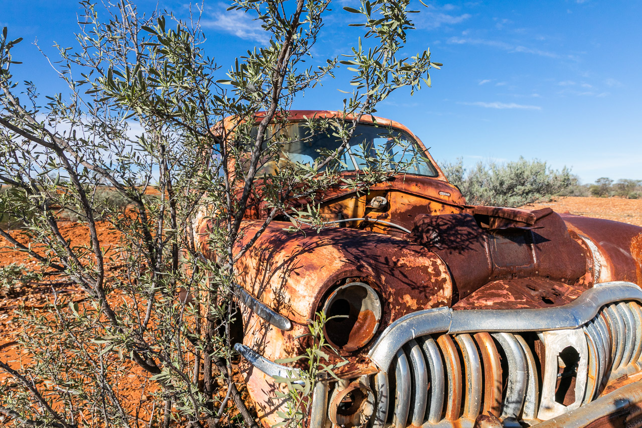 Old rusty vehicle and red dirt in the outback