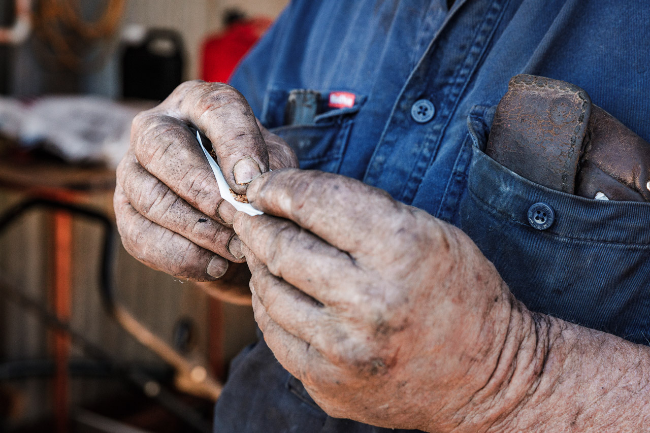 Man's oily hands rolling a cigarette