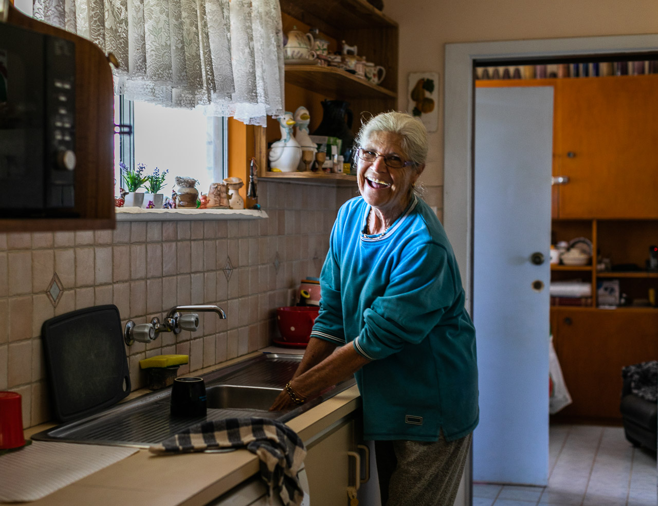 Elderly woman washing up in the kitchen