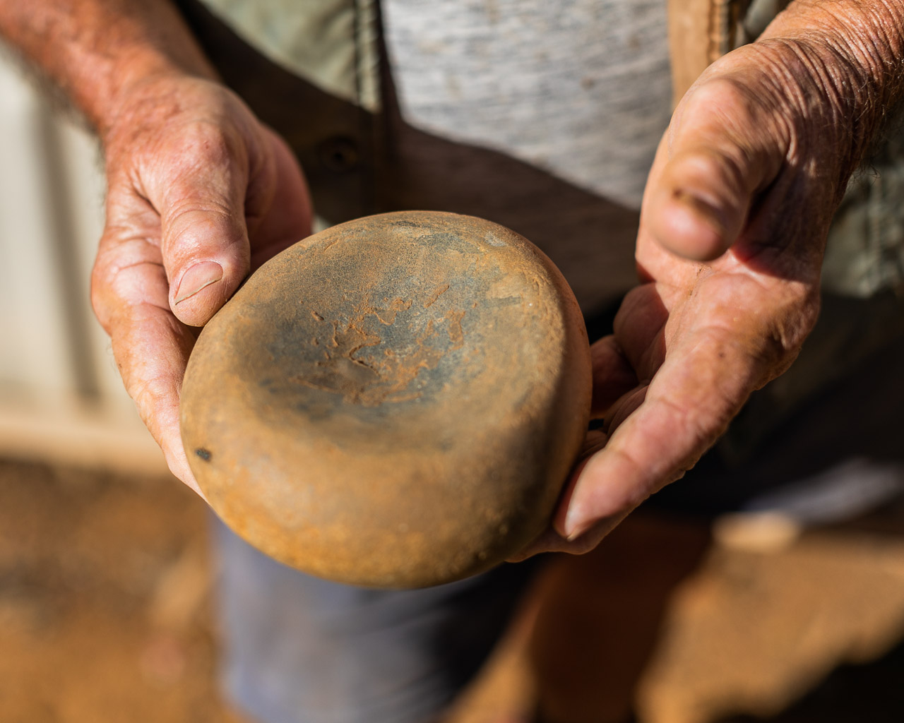 Aboriginal grind stone held in an old man's hands
