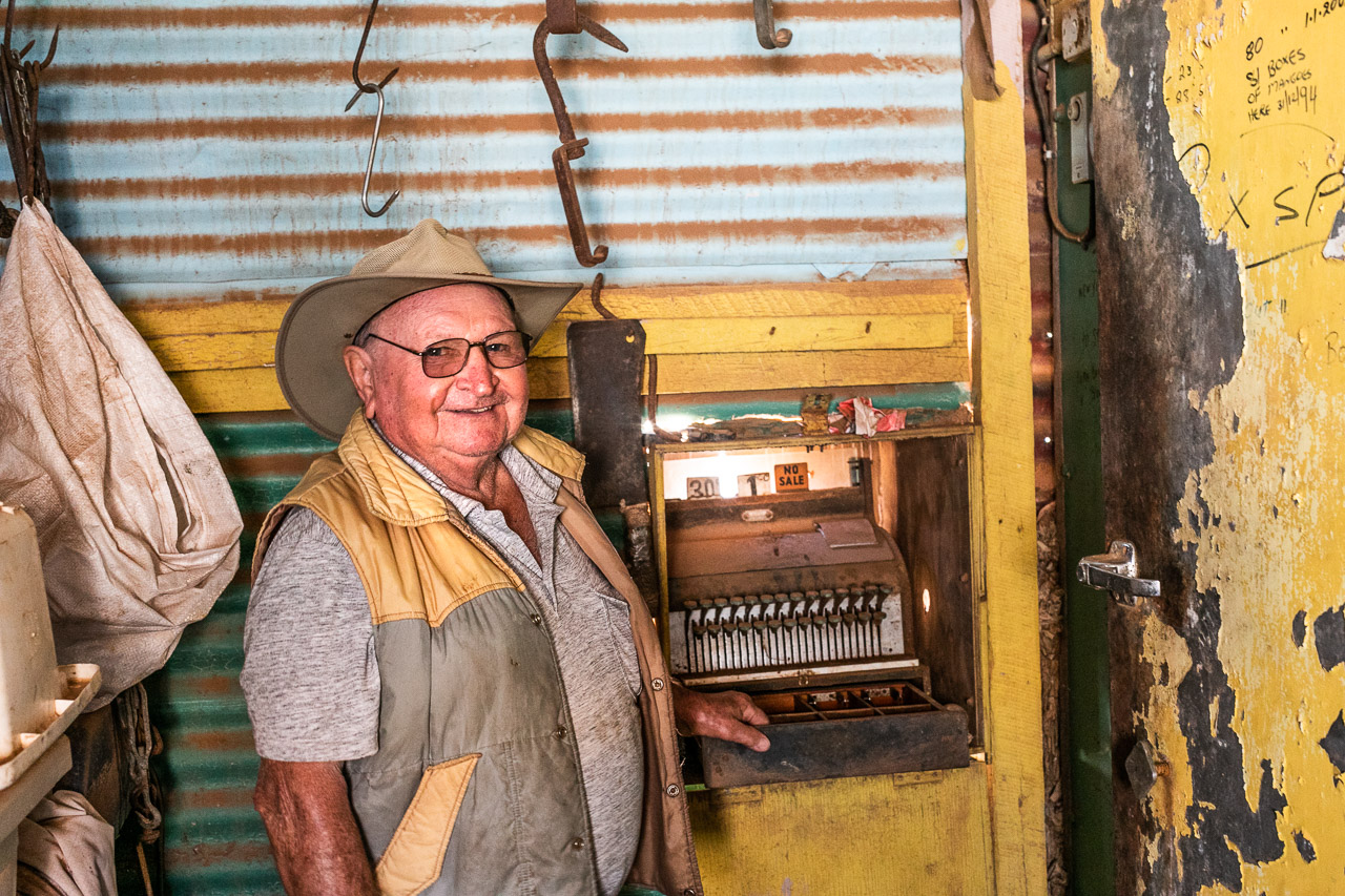 Man in his old shop with vintage till