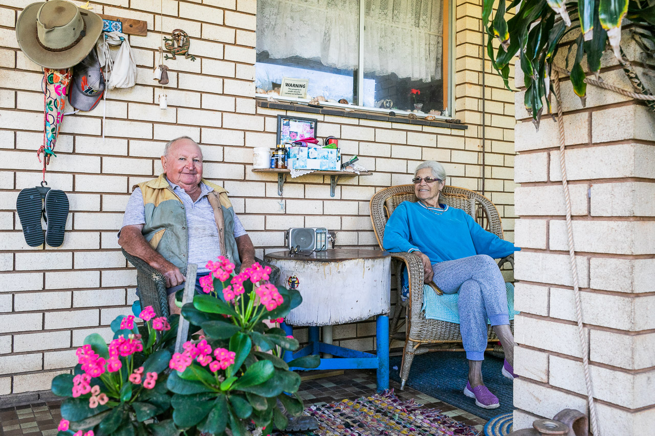 Old man and his wife sitting on their verandah surrounded by pot plants