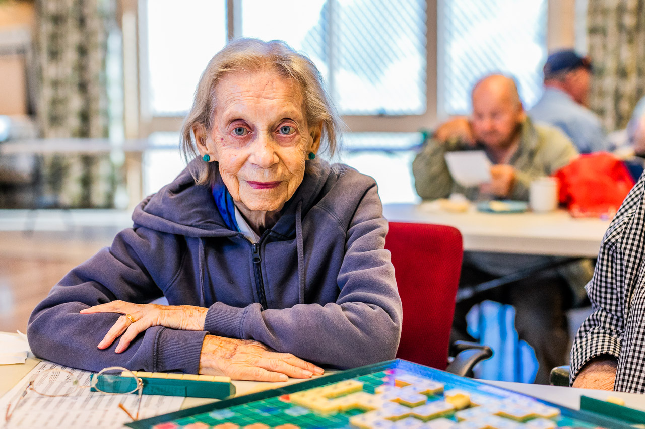 Elderly lady smiling and playing scrabble