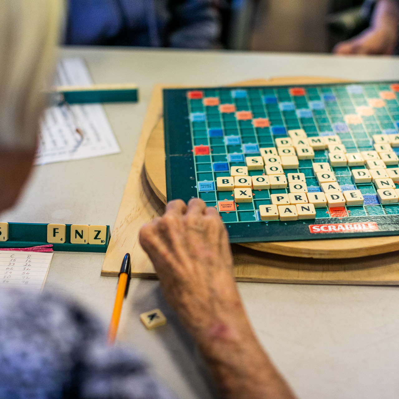 Old lady's hand a scrabble board