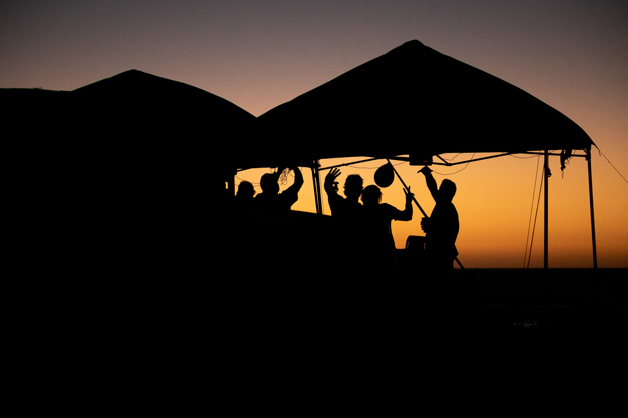 Silhouettes of men drinking beer at sunset