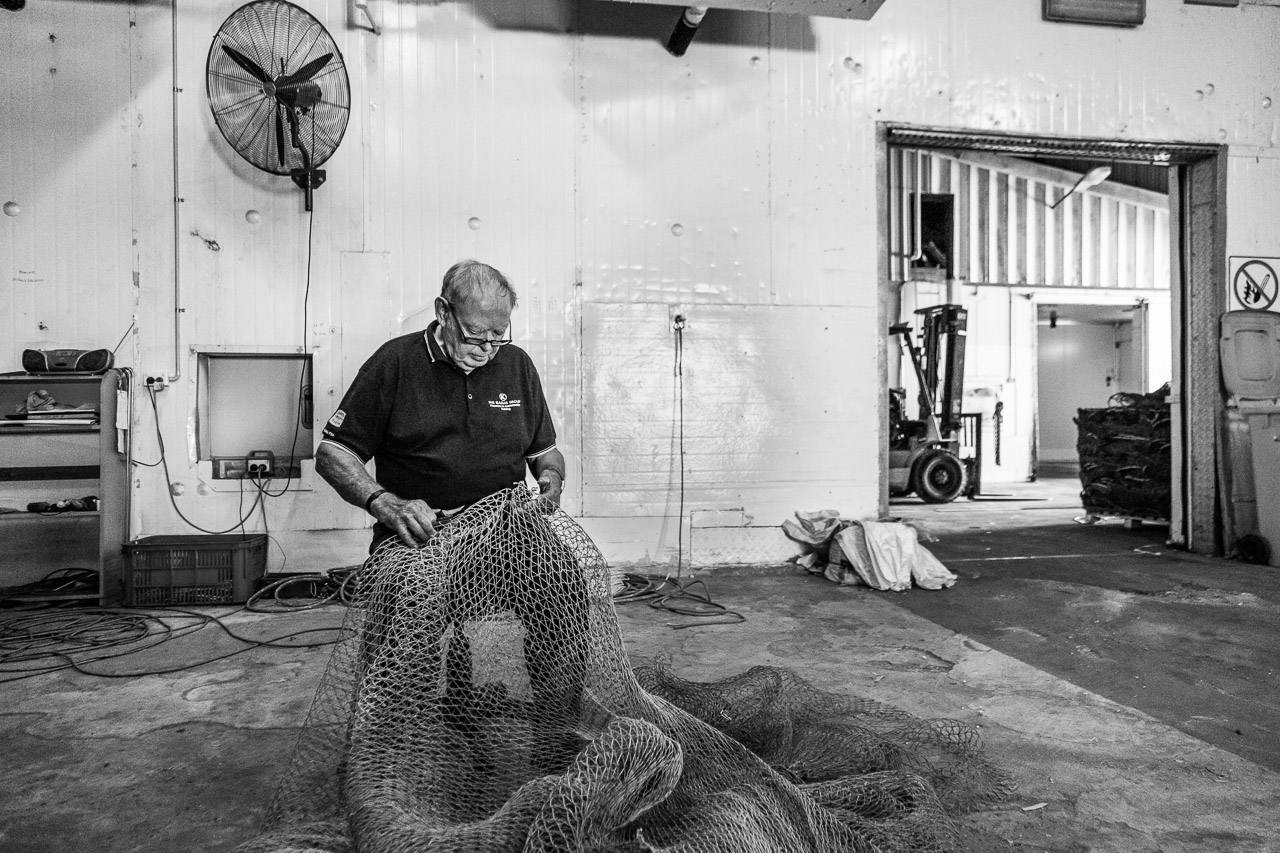 Fixing up holes in prawn nets at MG Kailis, Exmouth