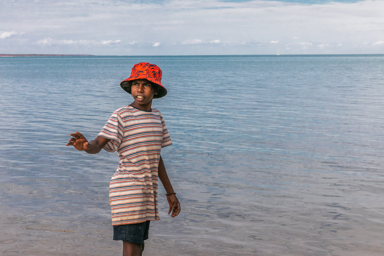 Indigenous boy in a red hat beside the ocean