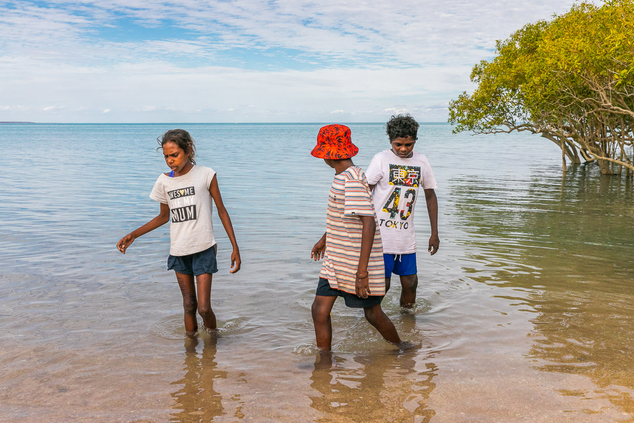 Three indigenous children in the bay by the mangroves in Broome, WA