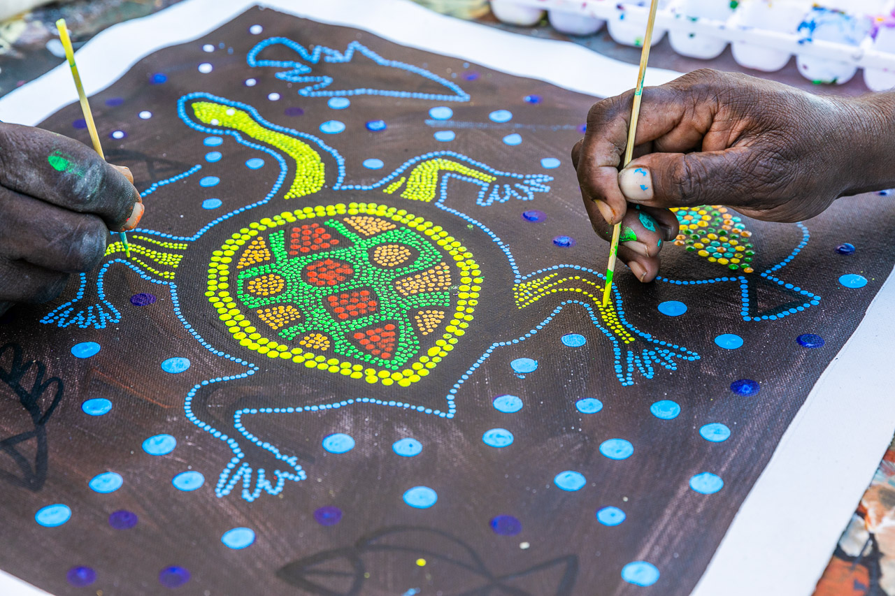 Two hands painting a long neck turtle at the Norval Gallery in Derby