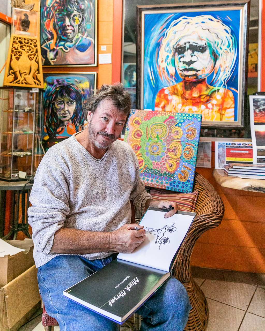 Artist Mark Norval signing a copy of his book in his Derby gallery in Western Australia