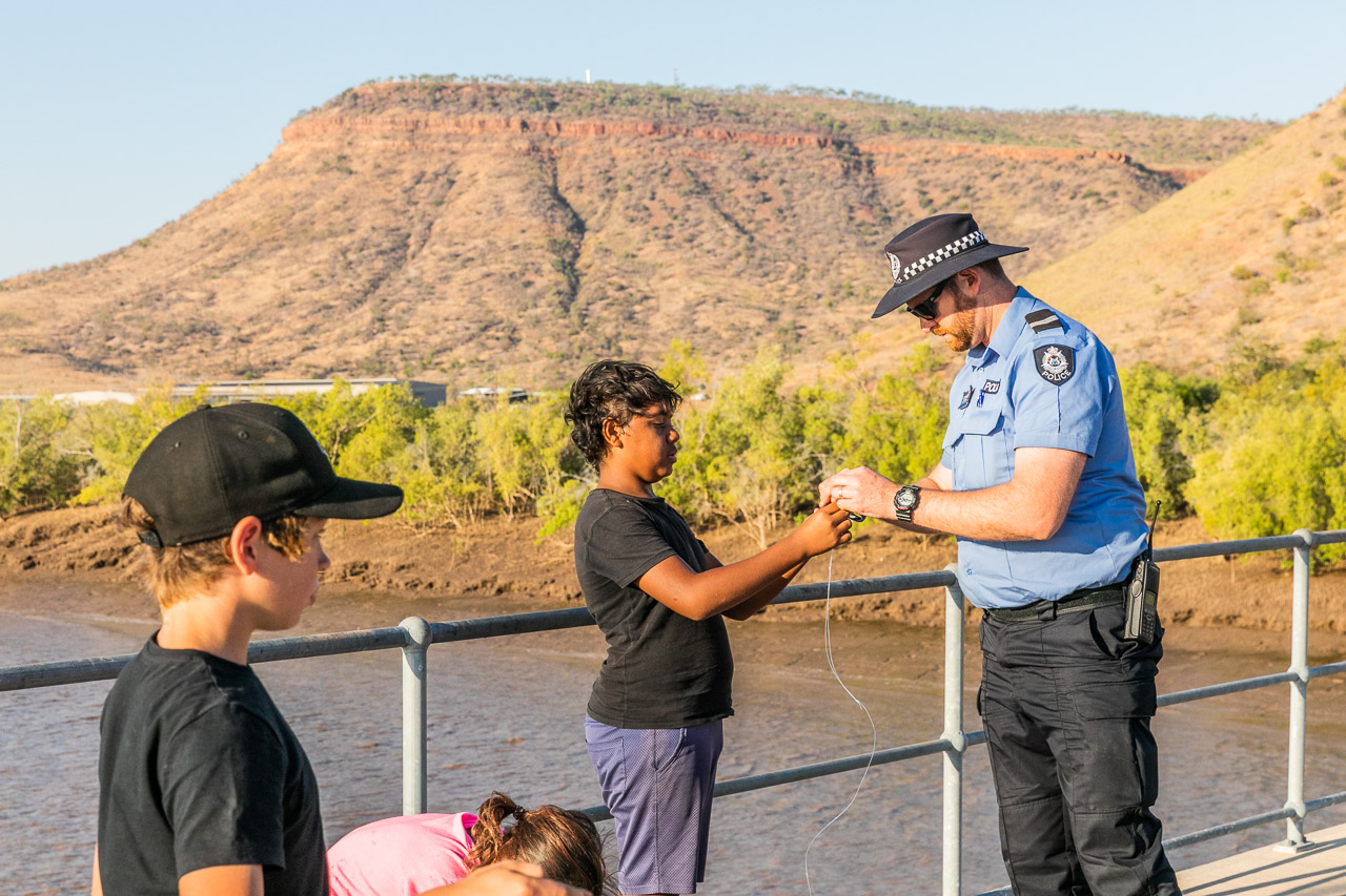 Police officer showing a boy how to put bait on his fishing line - this is community policing.