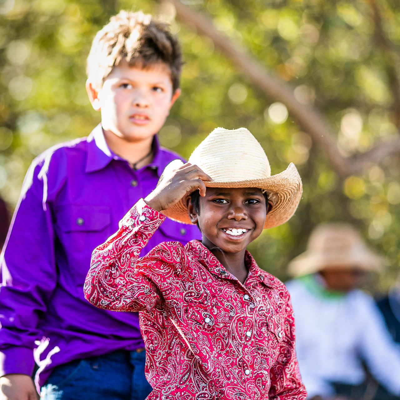 Aboriginal boy in a bright shirt and cowboy hat at the Broome Rodeo