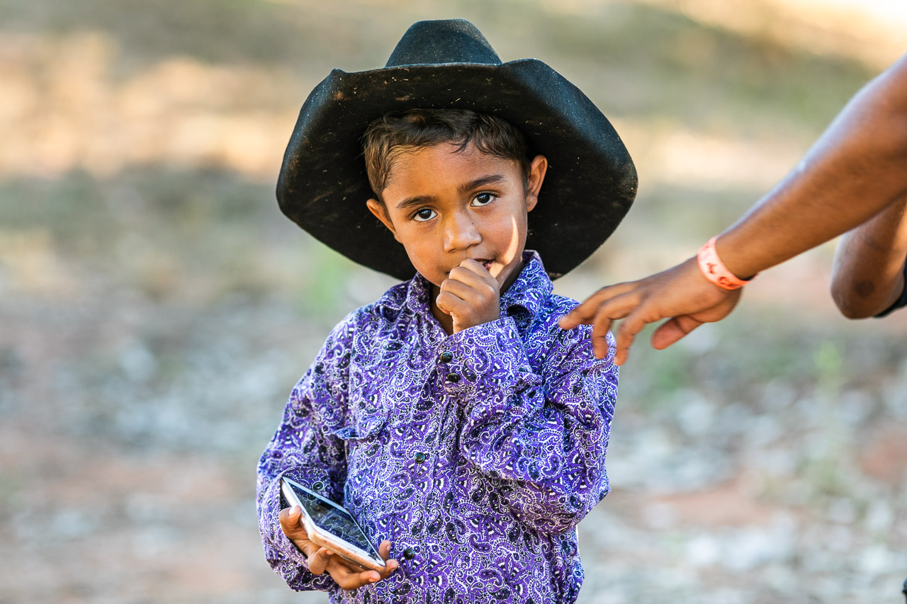 Aboriginal boy with a bright shirt, a black cowboy hat and a smart phone