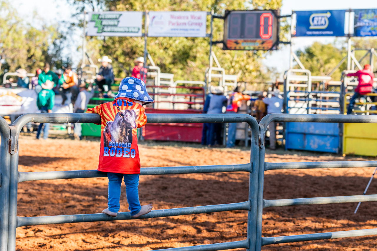 Small child standing on the railings at the Broome Rodeo 2019