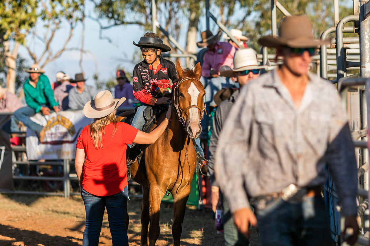 Child rider at the Broome Rodeo, on his horse and talking to an adult