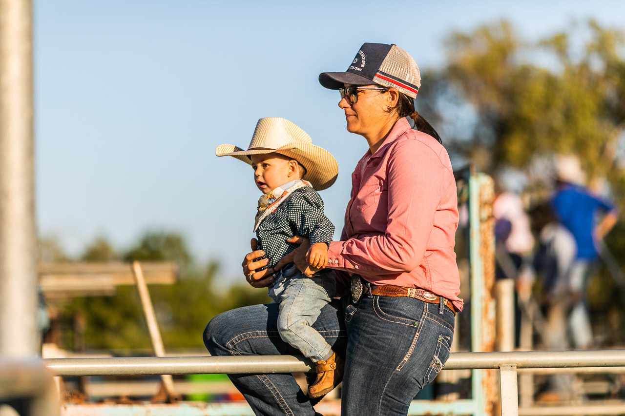 Baby dressed as a cowboy at the Broome Rodeo, sitting with his Mum on the railings