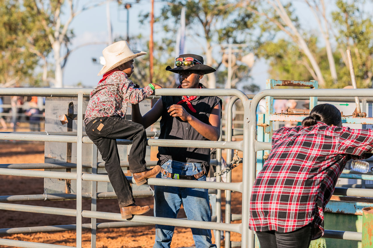 Man helping young boy climb over the railings at the Broome Rodeo