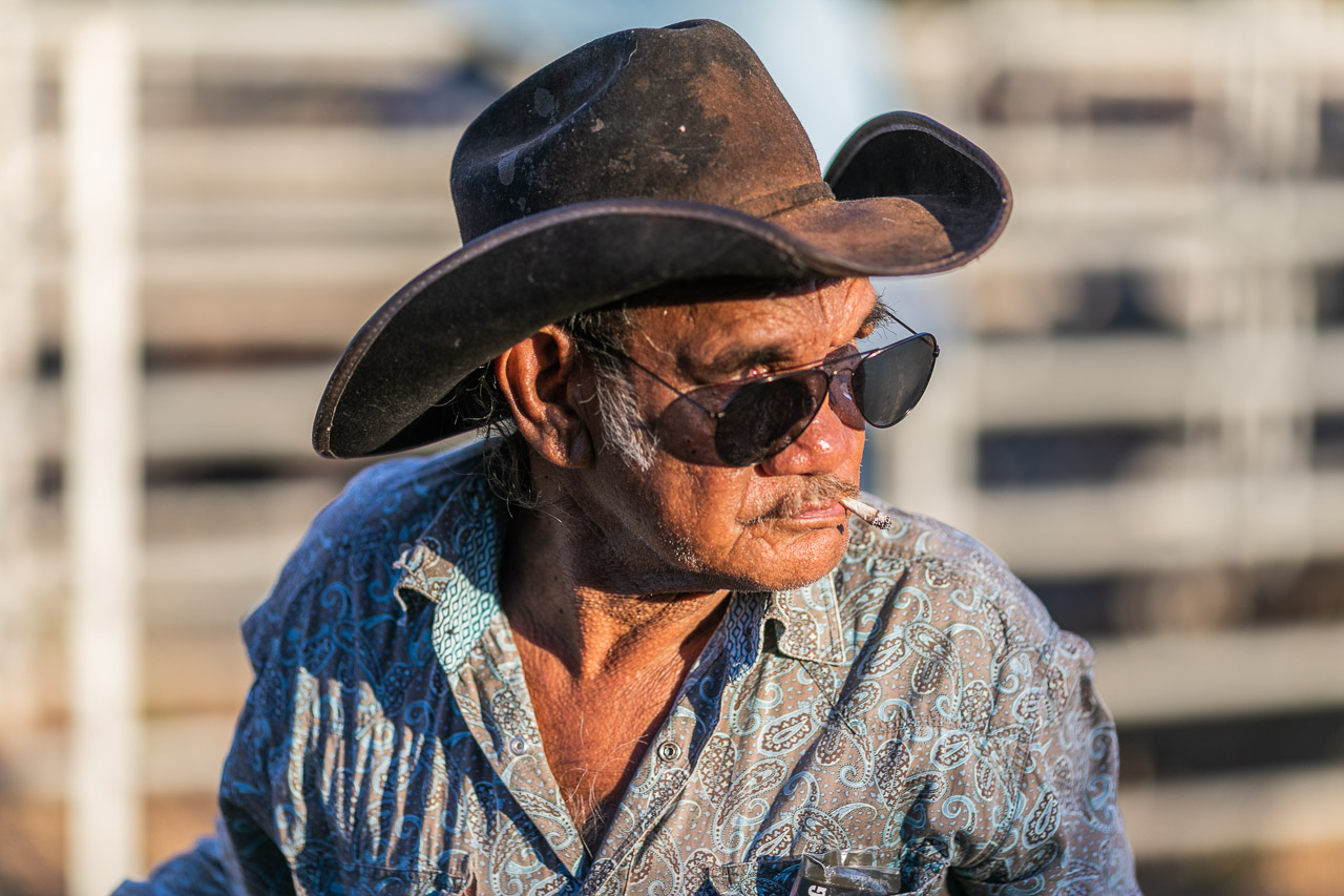 Old Aboriginal man wearing a cowboy hat and sunglasses, with a rollie cigarette in his mouth. Broome Rodeo 2019