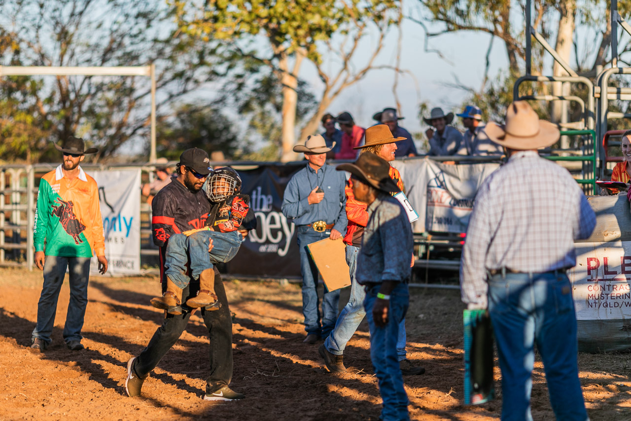 A young rodeo rider is carried out of the arena after a fall