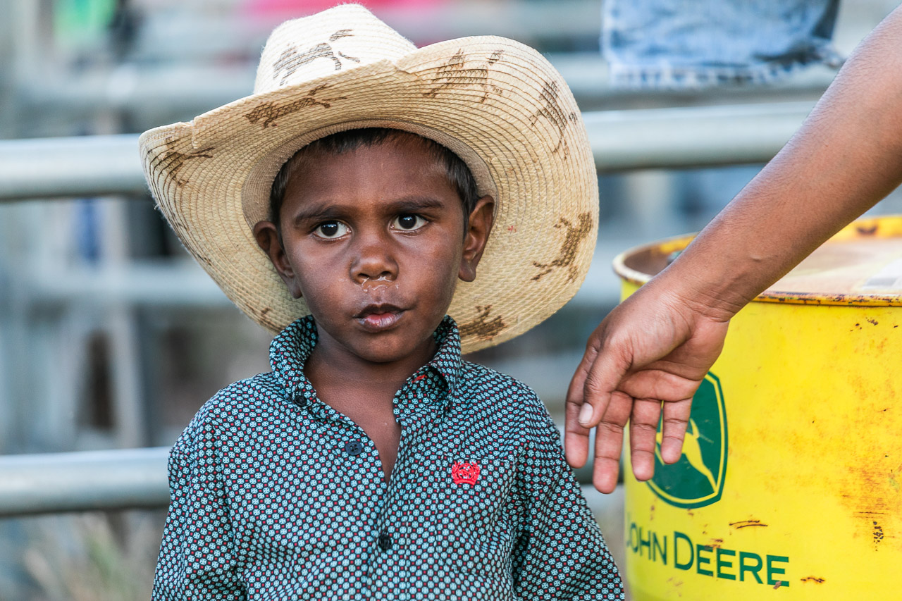 Young Aboriginal boy in a cowboy hat with a yellow and green barrel - Broome Rodeo 2019