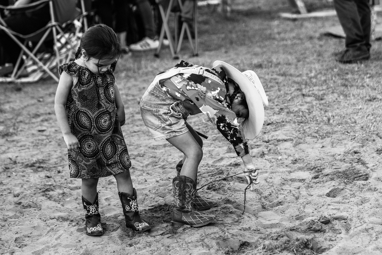Young girl wearing cowboy boots and cowboy hat, drawing in the dirt at the Broome Rodeo