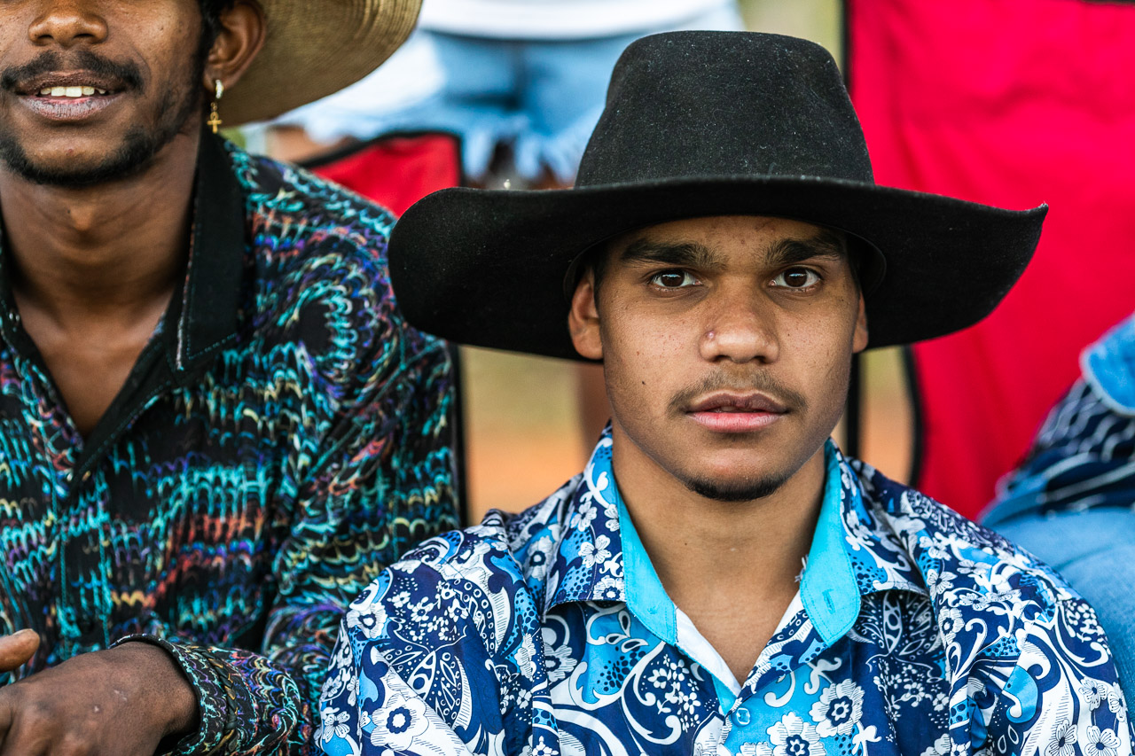 Young man in a bright shirt and a black cowboy hat at the Broome Rodeo