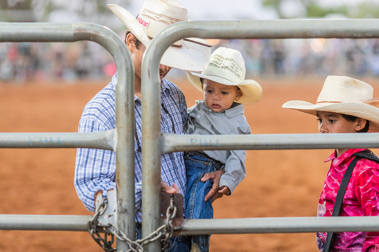 A father opens the metal gate at the Broome Rodeo, watched by his two children