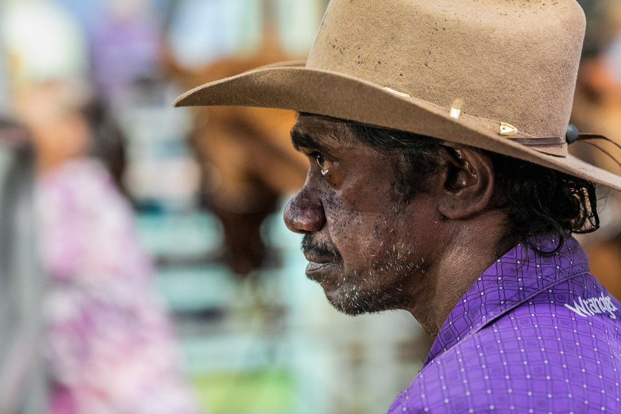 Profile portrait of an Aboriginal man wearing a cowboy hat and purple shirt