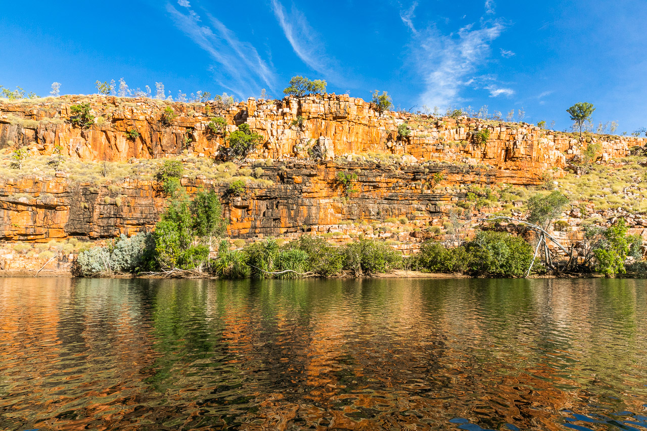 Deep red rocks reflected in the water at Chamberlain Gorge in the Kimberley