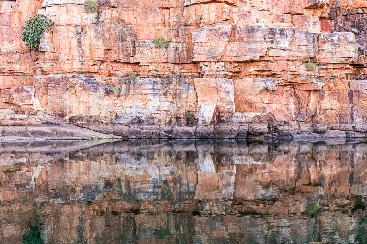 Red rocks reflected in still waters at Chamberlain Gorge, El Questro in the Kimberley region of Western Australia