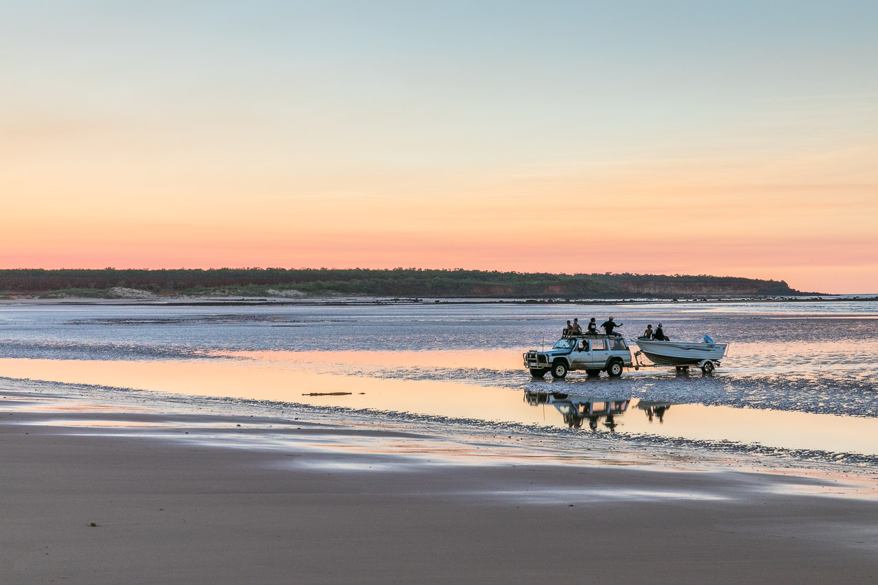Toyota landcruiser towing a boat on the sand flats at low tide on the Dampier Peninsula at sunset.