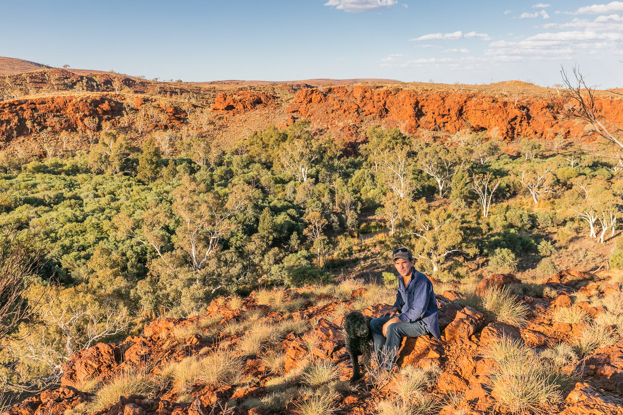A man and his black dog in the Pilbara, amongst native flora and red rocks