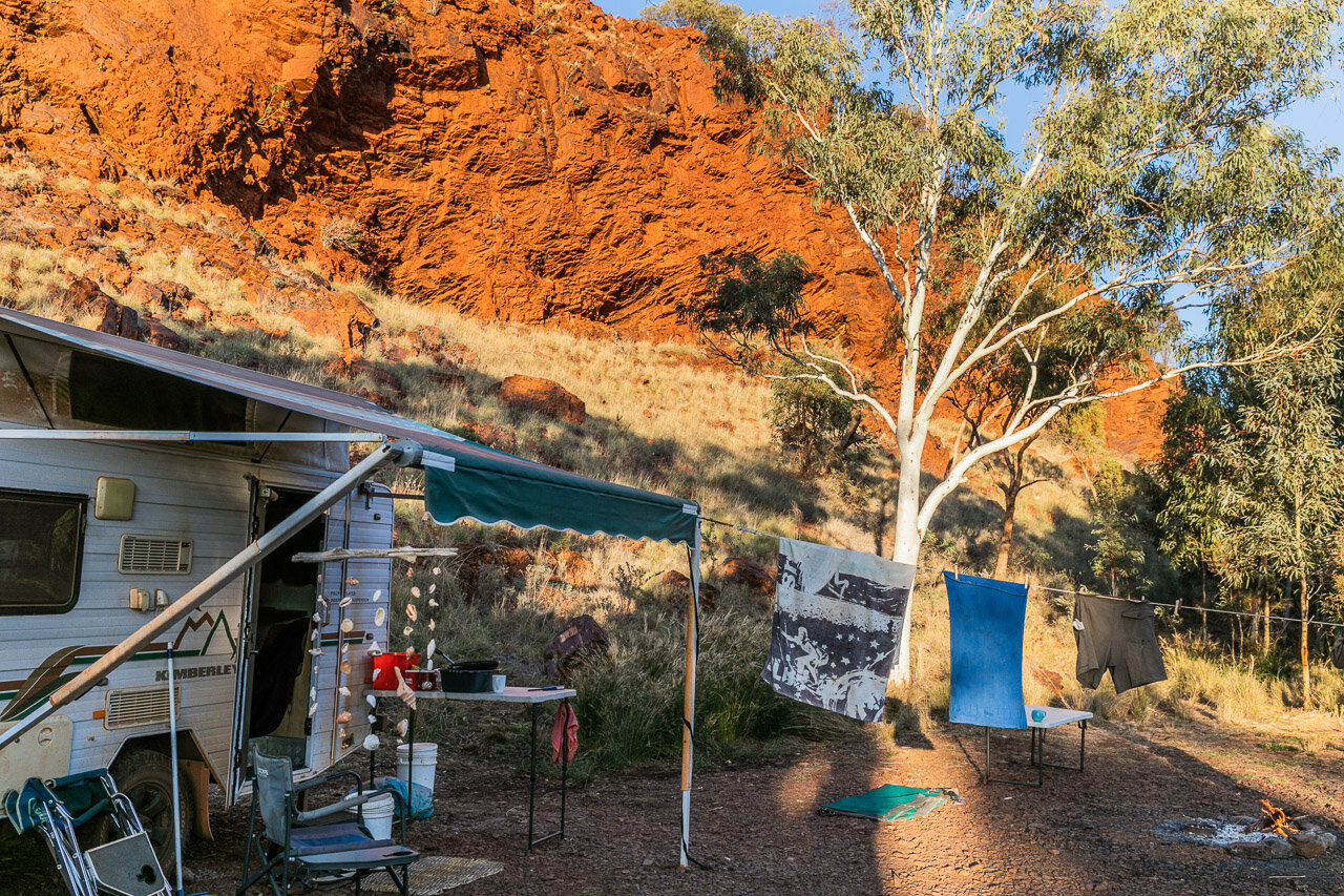 A secluded bush camp nestled in to the red rock cliff face