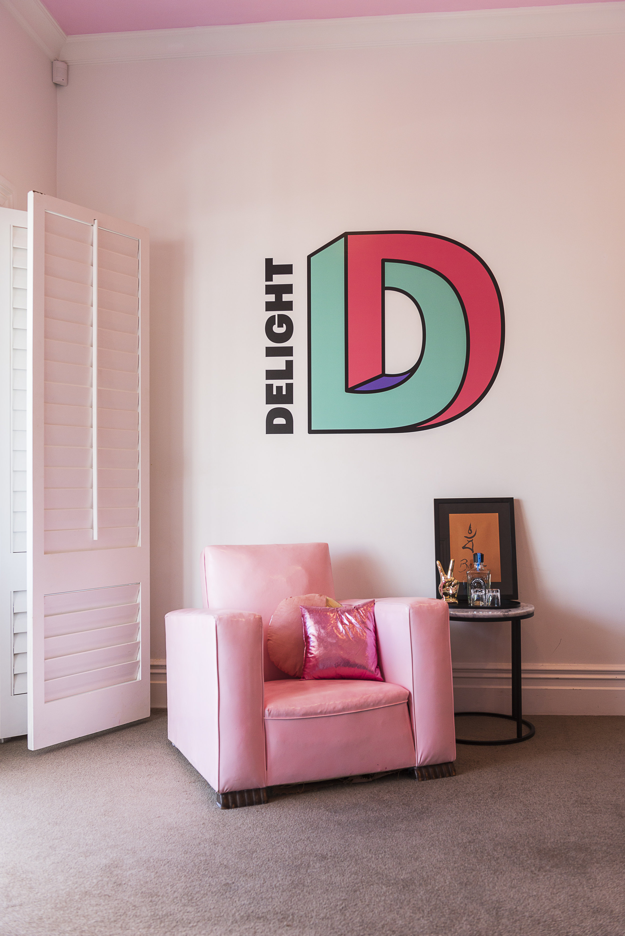 Delight's new logo provided the colour inspiration and made a fun wall decal in the main office above a custom painted Art Deco arm chair.  Photograph by Helen Bankers