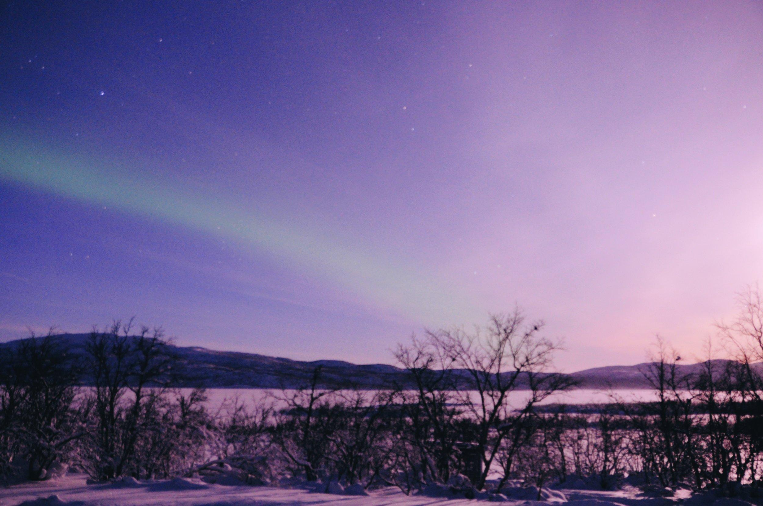 Zorza polarna niczym tęcza. Piękny widok. Poświata po prawej stronie pochodzi od księżyca.