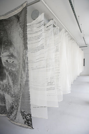 Image: Alex Younger,  Litigious , 20 document title pages from Constand v. Cosby, full 3 page Criminal complaint for the People of the Commonwealth of Pennsylvania v. Cosby, and Bill Cosby's mugshot on 23 screenprinted cotton cheesecloth panels and 1 jacquard-woven cotton panel, 42in x 60in each, 25ft long installed. Photo: Alex Younger.