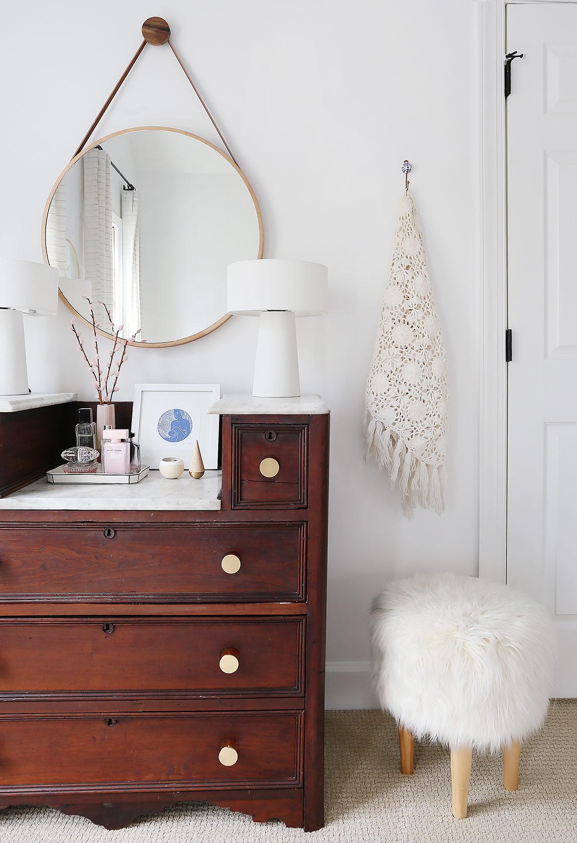 white lamps   /   round mirror   /   pink vase   /   brass pulls